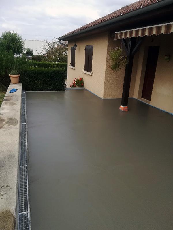 Construction de terrasse en béton lissé avec caniveau en bas de pente pour récupération de l'eau de pluie