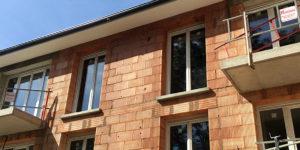 Construction de logements en Isère, façade en briques rouges avec balcons